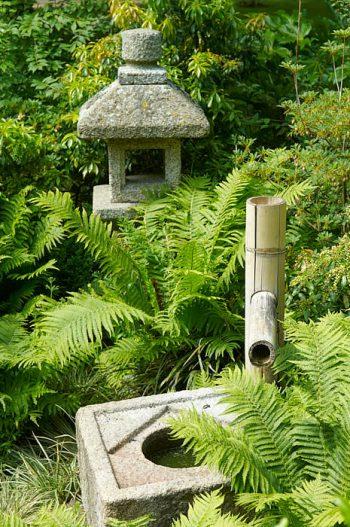 Lanterna och stenskål med bamburör för vattnet, japanska prydnader med ursprung i te-ceremonin.