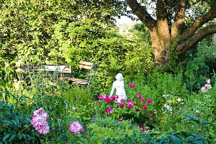 Pioner, rosor och en sittgrupp under ett äppelträd, den romantiska trädgården hemma hos konstnären Maria Björklund på Österlen. Statyetten gör illustrationen fullkomlig.