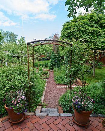 Örtagården skär diagonalt genom östra trädgården. Genom en portal träder man in. Klotlönnen bildar tak mot himlen.