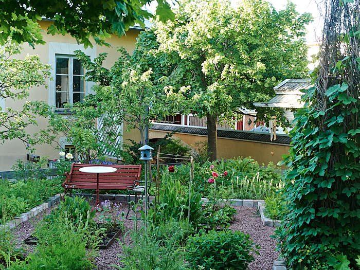 Ett klassiskt rutnätsmönster används för örtagården, från början i trä nu utbytt mot hållbart järn. Humlen till höger stärker rumsbildningen.